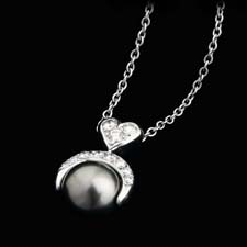 Platinum, diamond, and black tahitian pearl pendant from Gumuchian's ''Moonstruck'' line. .35ctw of diamonds top a 9.0mm black pearl. A nice way to give her your heart by the light of the moon.