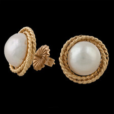 Gorgeous 14kt yellow gold and mabe pearl earrings. The earrings feature post backs and an intricate braided gold look. The pearls measure 11mm.