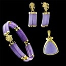 A very pretty 14kt gold suite of matching Lavender Jadeite. The bracelet is 7 1/4'' x 10mm, earrings 1'' x 10mm, and pendant 1'' by 17.5mm. Circa 1970's Looks like it has never been worn! Sold as set only for all Jadite matches.  Great buy for this price.