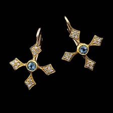 These beautiful 18kt yellow gold cross earrings are embellished with diamonds and aquamarine center stones.