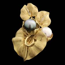 18kt yellow gold floral design with diamond pave accents and one each a black and a white south sea pearl