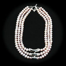 069CO3 - Three strand of Pink Pearl necklace with sterling silver accent tubes in the center of the piece and a sterling silver toggle clasp.