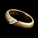 Designed by George Sawyer, a 5mm wedding band with three channel set diamonds weighing .08ct. The ring is made with 18kt yellow and red gold with 14kt grey gold and sterling silver.