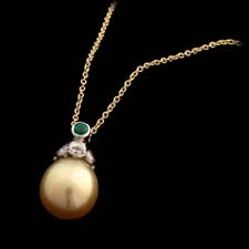 18kt white gold pendant with a 10.5mm golden pearl .40cts of diamonds and .10cts of emerald suspended from an 18kt yellow gold chain