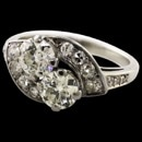A very pretty 14kt (stamped and tested) 1930's late Deco cross over diamond ring. The condition is excellent and there has never been repairs to this ring. The piece contains 14 single cut and full European cut diamonds set in the swirls flanking the two center diamond. The ring is set with one each (2 total) diamonds. One old European cut the other a transitional cut. The diamonds measure 5.35mm and 5.4mm each. The diamonds are clean SI + what we used to call top cape about J-K color but we did not remove the diamonds from the mounting. Estimated total weight 1.40ct. It is obvious this ring had been remounted from two rings, one around the turn of last century and the other the 1920. But, as a long time jeweler have rarely seen two generations of diamonds (formerly rings ) match up as this piece does. Overall you'll like it! Size 5.