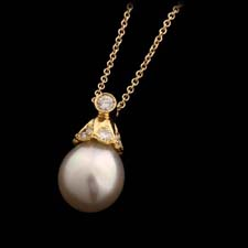 10mm White south sea pearl pendant with .35cts of diamonds set in 18kt yellow gold suspended from an 18kt yellow gold chain.