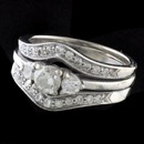 A ladies vintage 1980's diamond wedding set. The ring is a drop in e-ring with diamond band as follows. The band is set with 11 full cut diamonds on each side 22 diamonds total weighing approx.  .44ct The center ring is set with 3 diamonds.  2- .10ct ea, .20ct total and a .30ct center diamond. Total approx diamond weight .96ct.  The diamonds are VS clarity and H-I color. The ring is 14kt white gold and a size 5 1/2. 10.5mm to 4.7mm width.  Weight 6.6 grams.  Great condition.