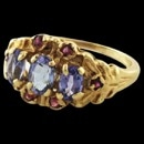 A very fine and very pretty natural Tanzanite and ruby finger ring circa 1980's. Set in the ring are 3 oval Tanzanites 1-5.5mm and 2 - 5.0mm Set around the center stones are 6 round very pretty red rubies. Not a commercial piece. Appears as a one of a kind castings. The ring is made of 14k gold and is a size 5.