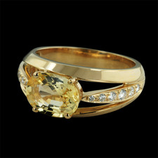 This Gumuchian Baby Luna ring is done in 18kt yellow gold with a rich yellow sapphire in the center. The sapphire measures 9x x 7m weighing 2.33ct. Pave' set along the shoulder are a total of 12 diamonds with a diamond weight of .18ct. 8mm width.