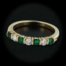 This gorgeous Jeff Cooper 18kt yellow gold band is set with .34cts of emeralds and .21cts of diamonds. With a thickness of 3.5mm and a size of 6 3/8.