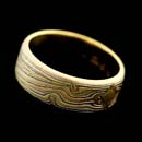 A 18kt-14kt, 8mm flat wedding band by George Sawyer, with a combination of red, yellow, and grey gold with sterling silver.