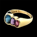 A 18kt gold ring by Kabana. The ring is set with a blue topaz (8x6mm) amethyst (6x4mm) and rhodolite garnet (5x3mm) The ring at the larget end measures 9mm in width. Size 7