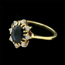 A fine 18kt gold natural sapphire and diamond ring. The ring is set with a medium dark pure blue sapphire weighing approx. 1.10ct. The sapphire is surrounded by 8 full cut VS F-G ideal cut diamonds weighing .24ct total The ring from the top measures 12.0mm x 10.0mm. Shank is a petite 1.25mm. Size 6 1/4