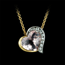 Heart shaped two tone 18K yellow gold and platinum necklace with a 4.93ct. Rose quartz center stone. Features 11 channel set round diamonds. This heart pendant also has a surprise diamond and pink sapphire set in the sides. The heart is 17mm wide and chain is 16
