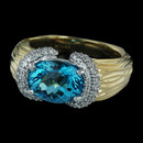 Facete collection from Spark in an 18 karat two tone ring. The ring is set with 0.42 carats in diamonds and a 2.95 carat oval blue topaz.